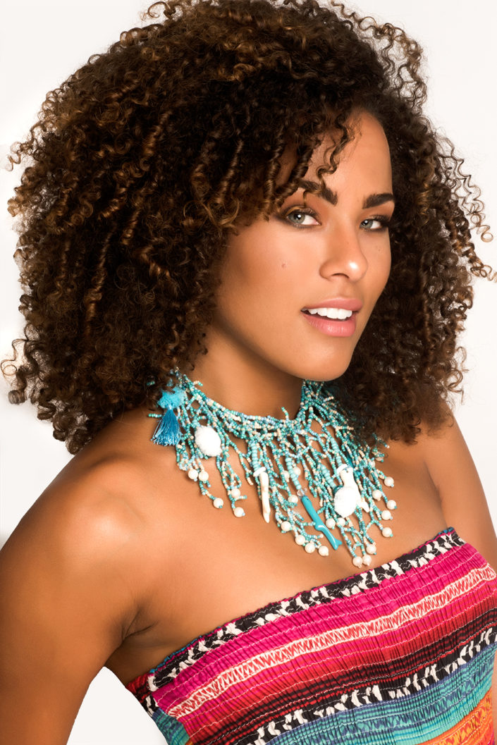 Pageant headshot by Delray Beach, Florida photography Debra Somerville. Young woman with brown ringlet curls with large beaded necklace and multicolored rusched top